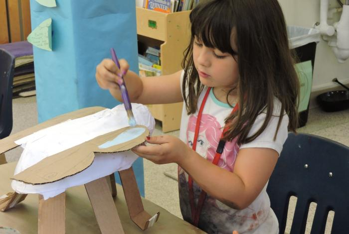 A child is sitting at a table painting her sculptural creation made out of cardboard.