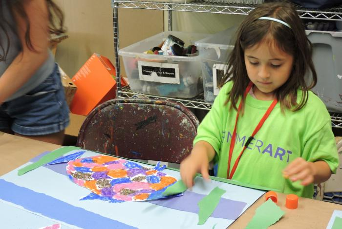 A child is working at a table, focused on her paper collage art project and not looking at the camera.