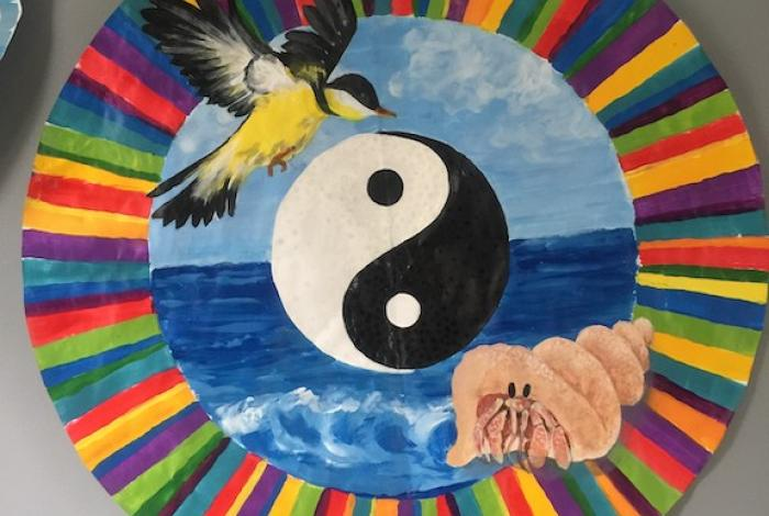 Artwork by Nanci Iovino. A bird hovers over a ying yang symbol in front of the ocean. A hermit crab in its shell sits at bottom right. The entire scene is encompassed by a rainbow striped circle border.