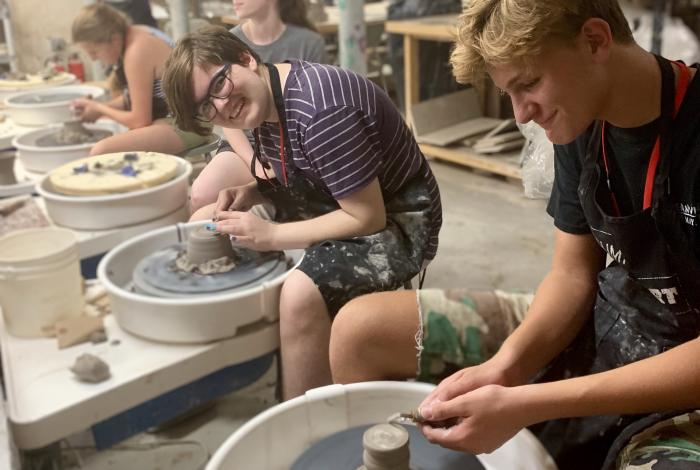 Four teens are sitting at a row of pottery wheels. They all have clay in front of them. One of them is looking and smiling at the camera.