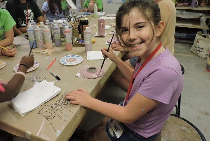 A young student is pausing while glazing one of her clay pieces to smile at the camera. She is glazing a wheel-thrown piece of stoneware at a large wooden table with other students.
