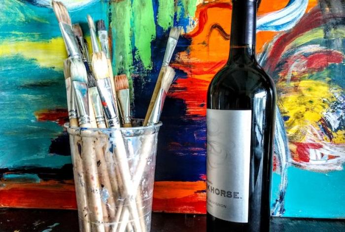 A cup of paint brushes is sitting next to a bottle of red wine. Both are in front of a colorful, abstract painting.