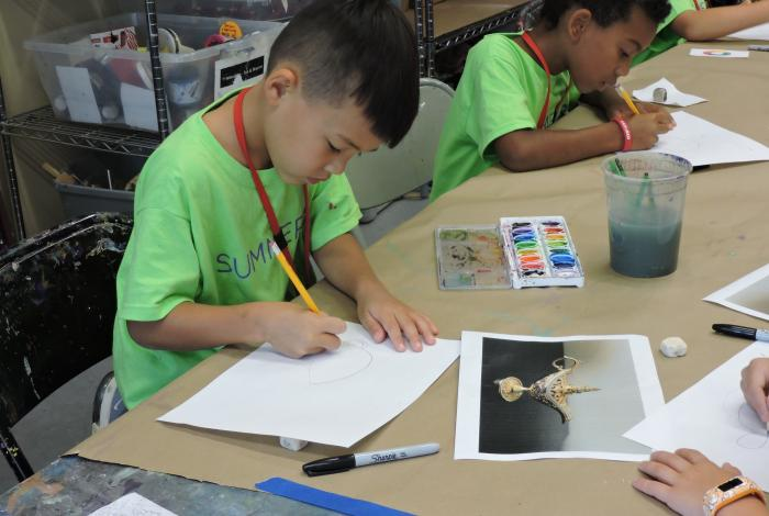 two young students are working on drawings at a table in a MAM studio.