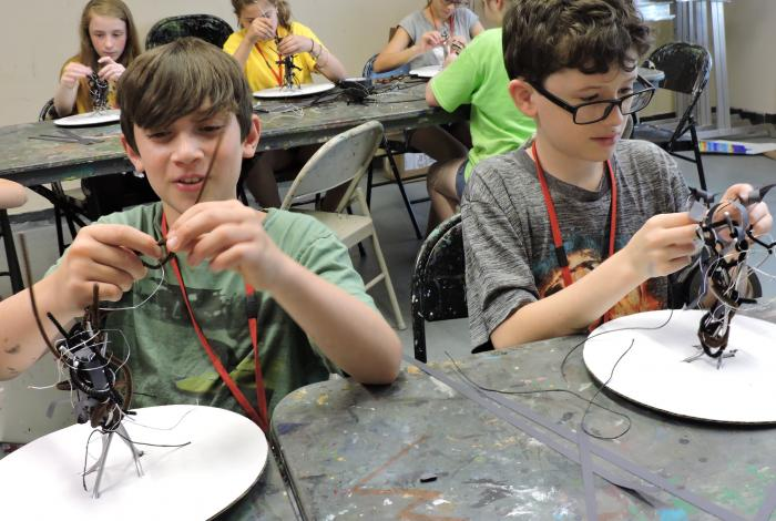 Two young students in a class are creating pipe cleaner sculptures in a MAM studio.