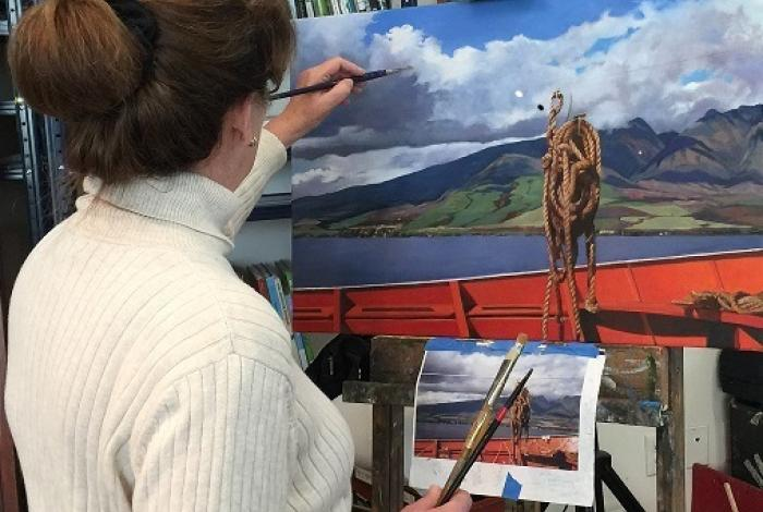A student is facing away from the camera, painting a lake and mountain scene on an easel.