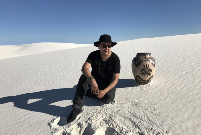 Virgil ortiz is sitting on a sand dune next to one of his elaborately decorated pots that is 1.5-2 feet tall.