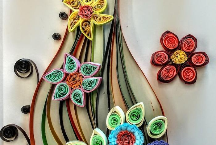A paper quilling project using paper of all the colors in the rainbow. It is a vase of flowers.