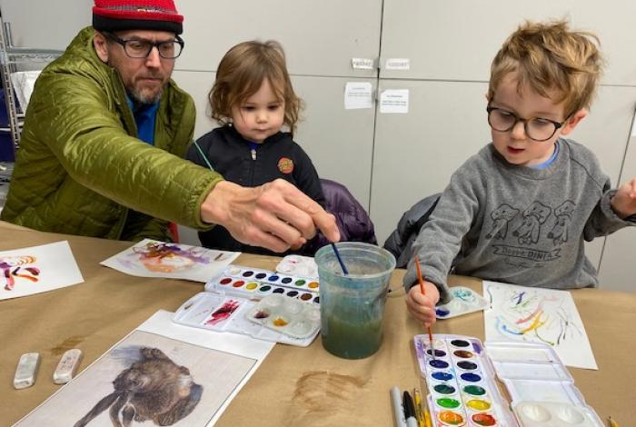 a family is working on painting projects alongside each other at a table in Drop-in studio.