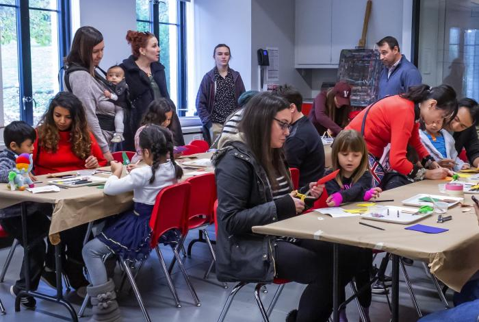 A room full of families work on art projects in the Geyer art studio at MAM.