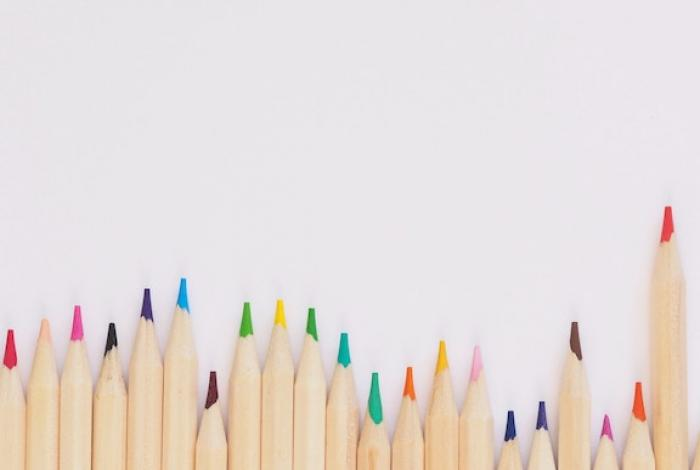 A row of assorted colored pencils laying on a white table.