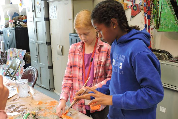 Two students are working together to paint a project on a table.