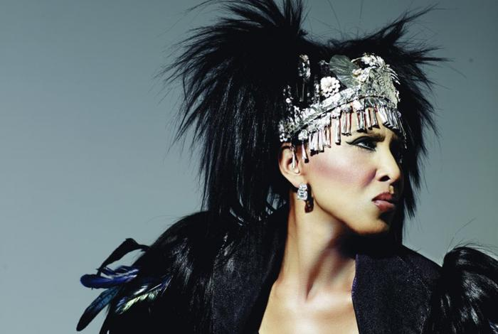 Nona Hendryx is posing in a professsional photo shoot with a metal headdress. she is not smiling, but looking very serious and off to the right, away from the camera.