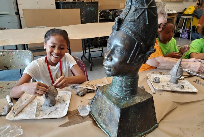 A camper is sitting at a table creating their own version of a large sculpture out of clay. She is smiling because she knows her picture is being taken, but she is looking at her work.
