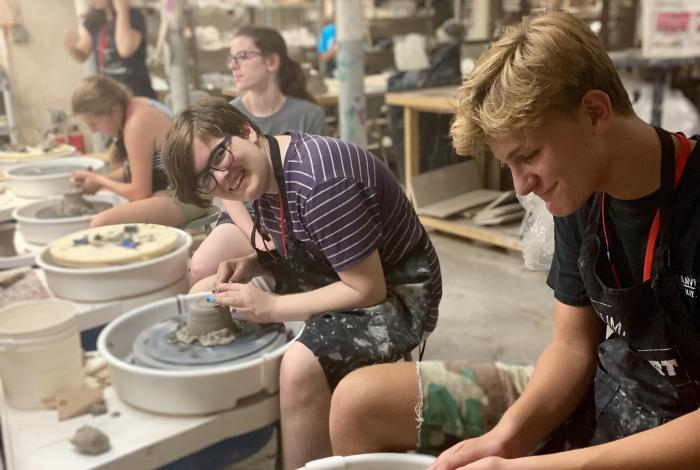 Teen campers are working on pottery wheels. One of them is smiling and looking at the camera. The rest of them are focusing on their work.