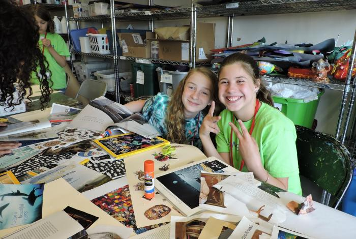 Two campers are sitting at a table covered in magazine clippings ready to be made into collages, They are both smiling for the camera. One of them is flashing the peace sign (holding up index and middle fingers).