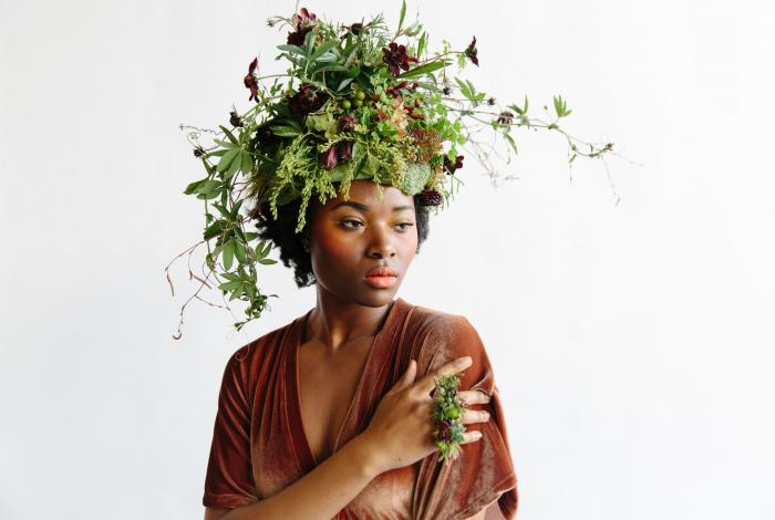 A woman poses against a white backdrop in a high fashion setting to show off a headdress and ring made of fresh flowers by Francoise Weeks. Photo by  Theresa Bear
