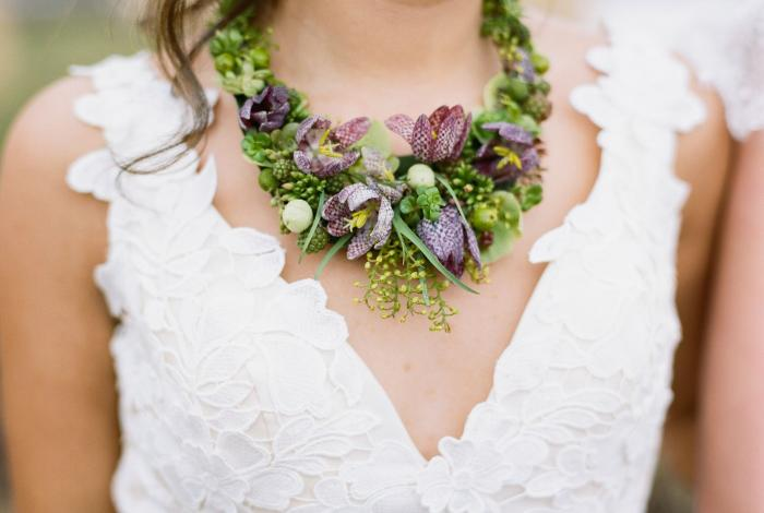 Close-up of a woman's neck and chest, showing a necklace made of fresh flowers by Francoise Weeks. Photo by Sarah Collier.