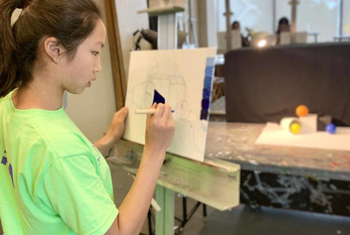 a teen student is working on a painting on an easel.