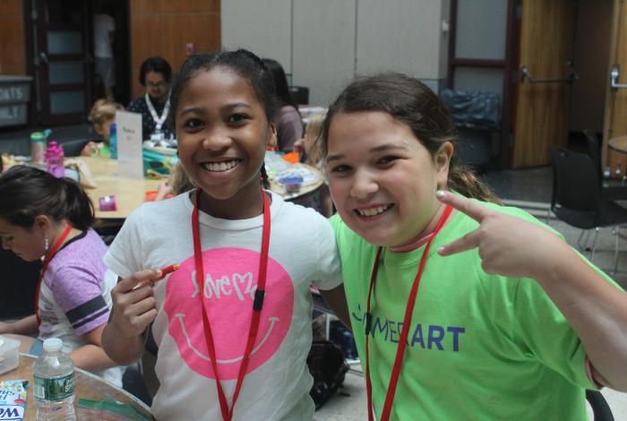 two campers are smiling for the camera. One of them is making the peace sign with her fingers.