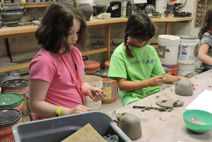 two young students are working on hand built clay pieces in the ceramics studio.