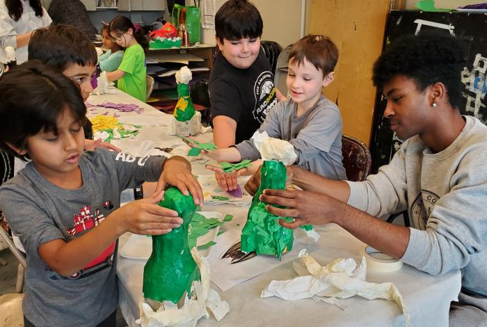 young students are working on papier mache projects at a table.