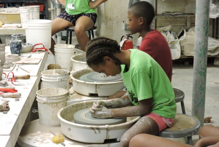 a pottery student is working on a project on the wheel.