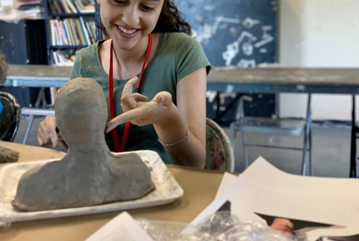 a teen student is working on a clay bust sculpture in class.