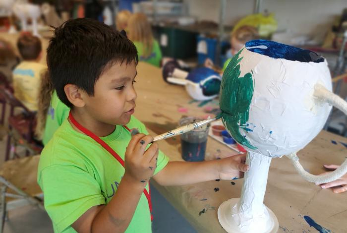 I'm an image! A student is painting a greek-inspired goblet made of papier mache.