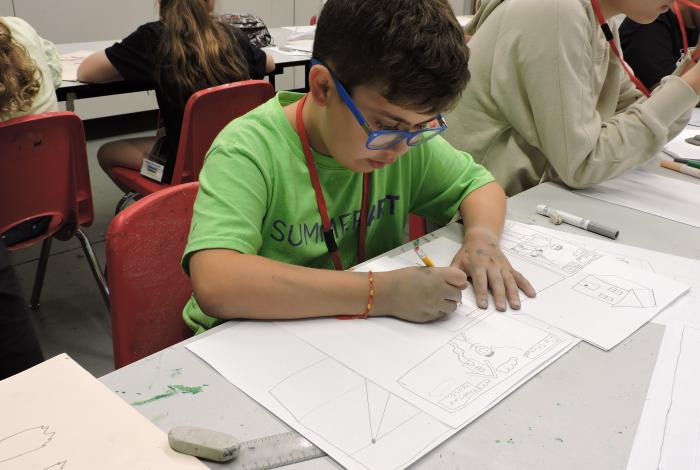 a student it drawing a comic strip on a large piece of paper. He is focused and looking at his work, not the camera.