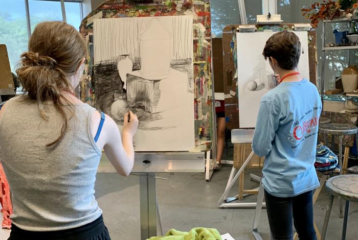 two teen students are drawing on easels. They are both facing away from the camera.