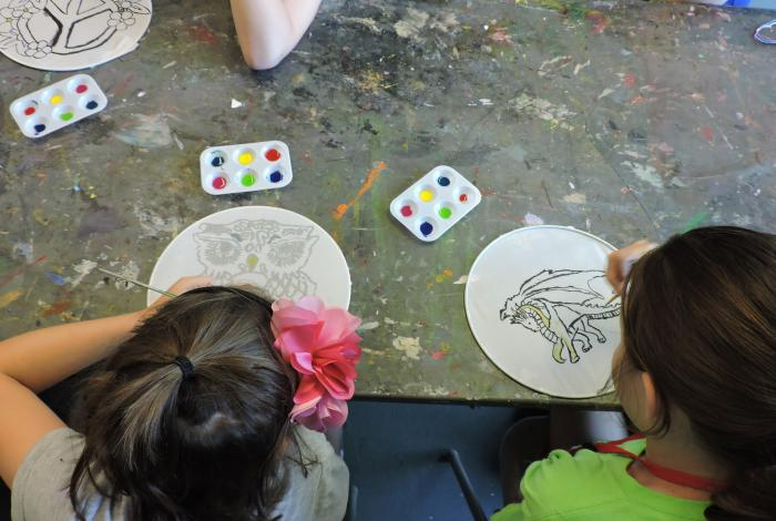 A view from above as two campers paint on silkscreens.