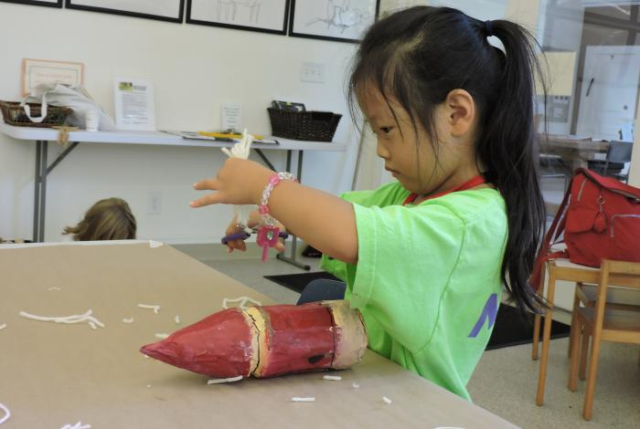 A young camper is cutting out tape to use in an art project.