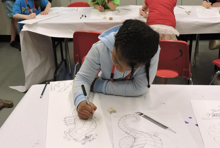 a camper is drawing sea creatures in a SummerART class. Her head is down and she is focused on her work.
