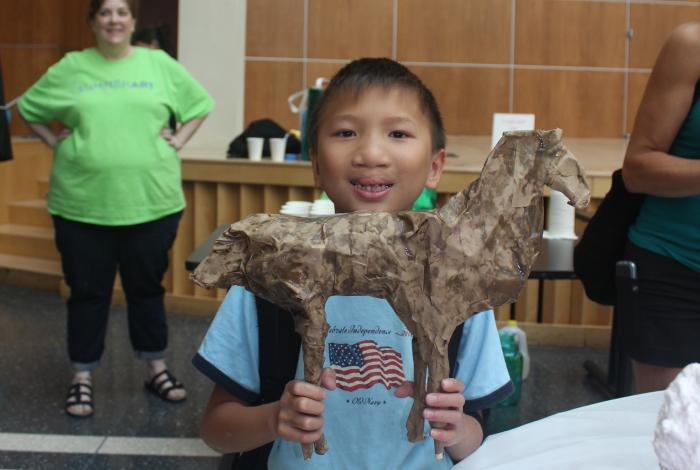 a young camper is holing up a papier mache horse that he made and smiling.