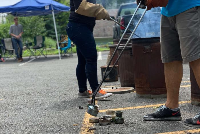 Two instructors are helping unload fired clay pieces out of metal pails with long metal tongs in the MAM parking lot during a Raku firing.