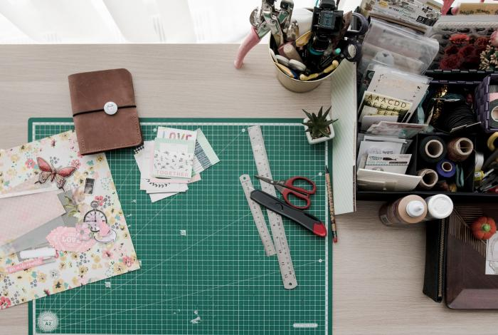 an image from above of a creative workspace or desk. Includes a cutting board, markers, paper scraps and more.