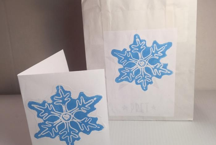 A bag and card with handmade snowflake stamps in blue.