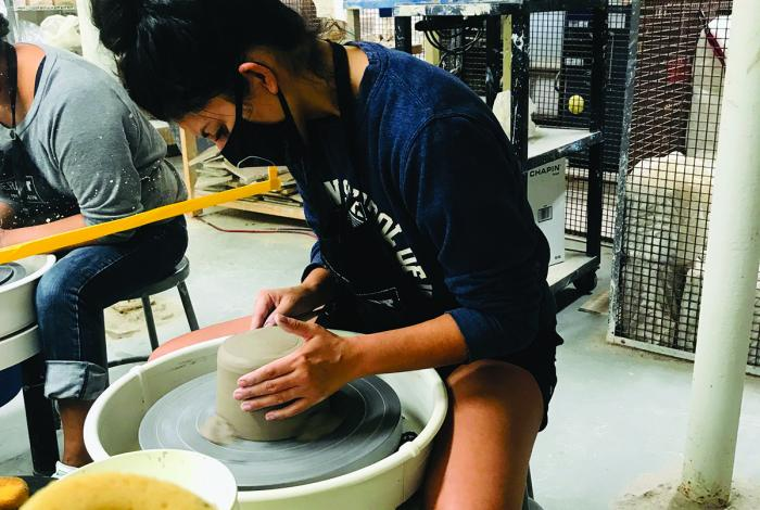 A teen is working on a pottery wheel.