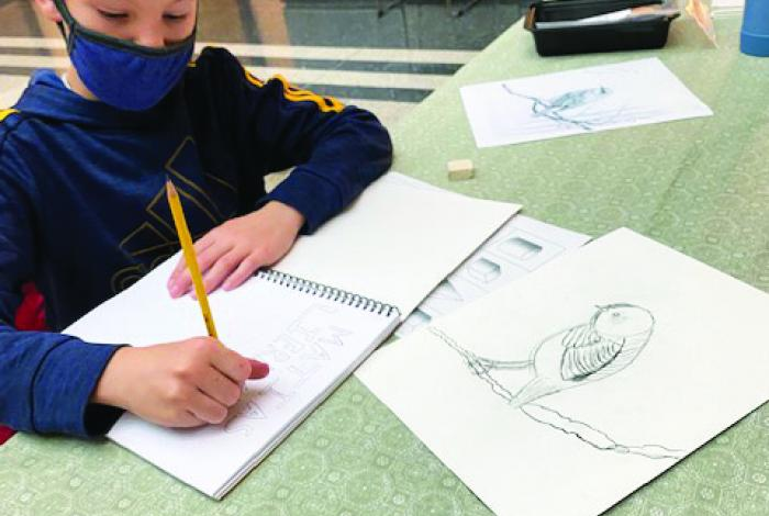 A student is drawing in a sketchbook