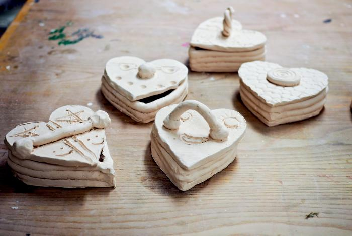 Five clay heart boxes with tops made by young MAM students
