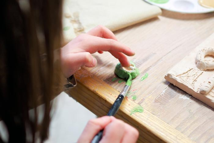 A child's hand painting glaze onto a clay piece