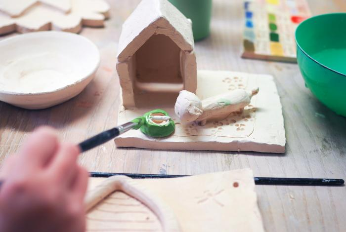 A child's hand painting glaze onto a clay doghouse.
