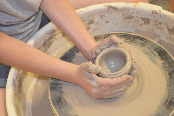 A student's hands working on the pottery wheel.