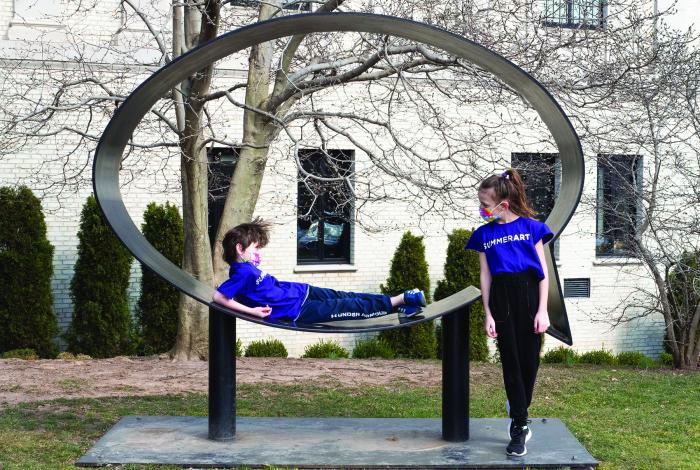 two students are hanging out on a sculpture at MAM.